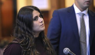 Standing beside her lawyer Ryan O'Neill, Nikki Yovino is sentenced one year in jail in Superior Court in Bridgeport, Conn. Thursday, Aug. 23, 2018 for making false rape accusations against two Sacred Heart University football players. Police say Yovino made up the claims because she thought the consensual encounter would damage her relationship with another student. (Brian A. Pounds/Hearst Connecticut Media via AP)