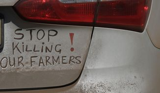 """FILE - In this file photo dated Monday, Oct 30 2017, a bumper sign calls for the end of farm killings in South Africa, during a blockade of a freeway in Midvaal, South Africa. U.S. President Donald Trump has tweeted that he has asked the U.S. Secretary of State Mike Pompeo to """"closely study the South African land and farm seizures and expropriations and the large scale killing of farmers."""" Trump added, """"South African Government is now seizing land from white farmers."""" (AP Photo/Themba Hadebe, File)"""