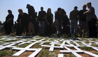 """In this photo taken Oct. 30, 2017 people place white crosses, symbolically representing farmers killed in the country, at a ceremony at the Vorrtrekker Monument in Pretoria, South Africa. U.S. President Donald Trump has tweeted that he has asked the Secretary of State Mike Pompeo to """"closely study the South African land and farm seizures and expropriations and the large scale killing of farmers."""" Trump added, """"South African Government is now seizing land from white farmers."""" (AP Photo)"""