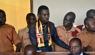Ugandan pop star-turned-lawmaker Kyagulanyi Ssentamu, also known as Bobi Wine, center, arrives at a magistrate's court in Gulu, northern Uganda Thursday, Aug. 23, 2018. Bobi Wine, who opposes the longtime president Yoweri Museveni, was charged with treason in the civilian court in Gulu on Thursday, minutes after a military court dropped weapons charges. (AP Photo)