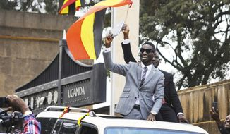 FILE - In this Tuesday, July 11, 2017 file photo, Ugandan pop star Kyagulanyi Ssentamu, better known as Bobi Wine, center, gestures to supporters shortly after being sworn in as a member of parliament in Kampala, Uganda. On Thursday, Aug. 23, 2018, Ugandan military prosecutors withdrew weapons charges against the jailed pop star and lawmaker who opposes the longtime president. (AP Photo/Ronald Kabuubi, File)