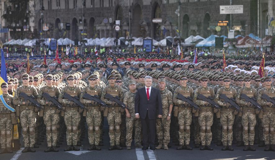 Ukrainian President Petro Poroshenko, center, poses for photo with soldiers during a rehearsal for the Independence Day military parade in Kiev, Ukraine, Wednesday, Aug. 22, 2018. Ukraine will mark the 27th anniversary of the Independence Day on Aug. 24. (Mikhail Palinchak/Presidential Press Service Pool Photo via AP)