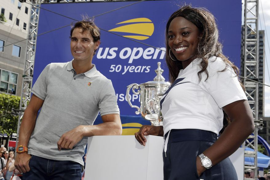Defending champions Rafael Nadal and Sloane Stevens pose with the tournament's trophies during the reveal of the 2018 U.S. Open draw in New York, Thursday, Aug. 23, 2018.  (AP Photo/Richard Drew)