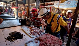 In this Aug. 19, 2018 photo, a customer smells a piece of spoiled meat at a market in Maracaibo, Venezuela. Venezuelans are lining up at one of the country's largest markets to buy spoiled meat. It makes some sick, but at bargain prices, it's the only way they can afford beef. (AP Photo/Fernando Llano)