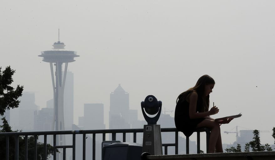In this Aug. 14, 2018 file photo, a girl works on a drawing next to an unused viewing scope as a smoky haze obscures the Space Needle and downtown Seattle behind. (AP Photo/Elaine Thompson, File)
