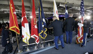 United States, Texas and military flags are removed following an activation ceremony for the U.S. Army futures Command on Friday in Austin, Texas. The headquarters will be located at the University of Texas Systems Building in Austin. (Associated Press)