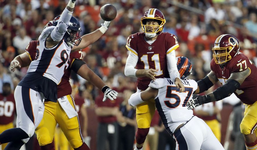 Washington Redskins quarterback Alex Smith (11) throws the ball as he is hit by Denver Broncos defensive end DeMarcus Walker (57) with defensive end Derek Wolfe (95) nearby, during the first half of a preseason NFL football game Friday, Aug. 24, 2018, in Landover, Md. (AP Photo/Alex Brandon)
