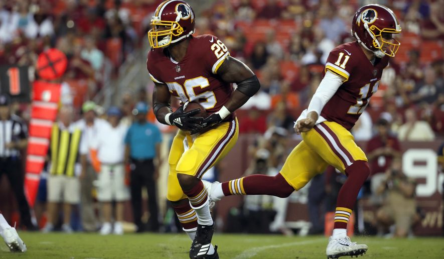 Washington Redskins running back Adrian Peterson (26) takes the handoff from Washington Redskins quarterback Alex Smith (11) during the first half of a preseason NFL football game against the Denver Broncos, Friday, Aug. 24, 2018, in Landover, Md. (AP Photo/Alex Brandon)