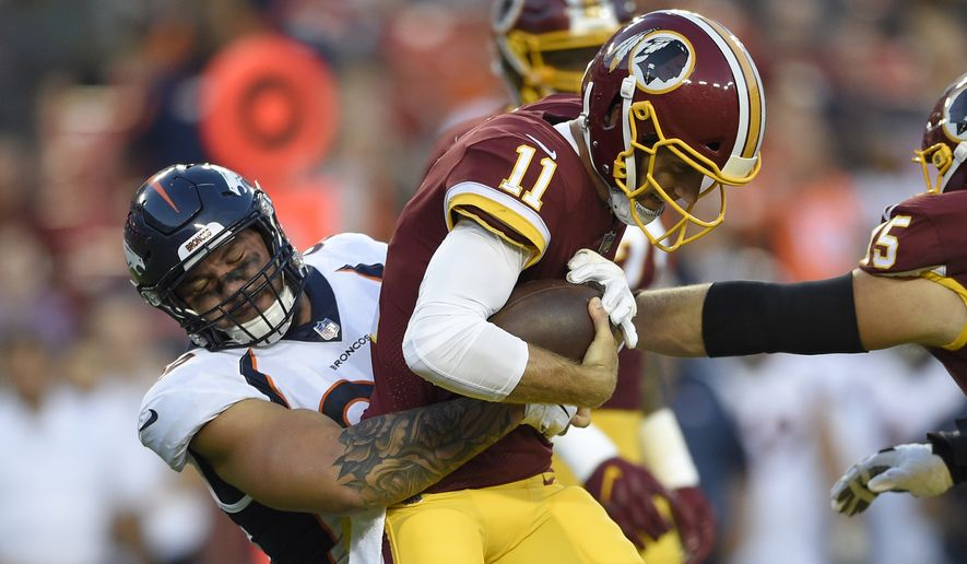 Washington Redskins quarterback Alex Smith (11) is sacked by Denver Broncos defensive end Adam Gotsis, left, during the first half of a preseason NFL football game Friday, Aug. 24, 2018, in Landover, Md. (AP Photo/Nick Wass)