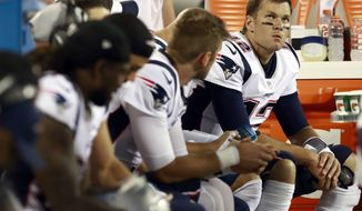New England Patriots' Tom Brady (12) watches from the bench with teammates during the second half of a preseason NFL football game against the Carolina Panthers in Charlotte, N.C., Friday, Aug. 24, 2018. (AP Photo/Jason E. Miczek)