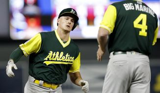 Oakland Athletics' Matt Chapman is congratulated by Athletics' third base coach Matt Williams (4) after hitting a three-run home run against the Minnesota Twins in the eighth inning during a baseball game Friday, Aug. 24, 2018, in Minneapolis. (AP Photo/Andy Clayton-King)
