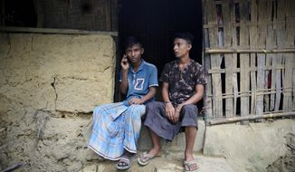 """In this Thursday, Aug. 23, 2018 photo, 15-year-old Rohingya refugee Abdullah Razzaq, speak on the phone to his mother who still lives in Myanmar, as his elder brother Abdur, 17, sits beside him at Kutupalong refugee camp, Bangladesh. """"Mummy! Mummy!"""" Razzaq shouted to his mother earlier this week in their once-a-week call, nearly a year after he and his brother, along with more than 700,000 other Rohingya Muslims, fled waves of attacks by Myanmar security forces and crossed the border into Bangladesh. """"Why don't you guys come here?"""" (AP Photo/Altaf Qadri)"""
