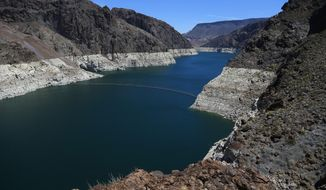 FILE - In this May 31, 2018, file photo, the low level of the water line is shown on the banks of the Colorado River in Hoover Dam, Ariz. U.S. officials say the chances of a shortage in the vital Colorado River system have risen to 57 percent in 2020. (AP Photo/Ross D. Franklin, File)