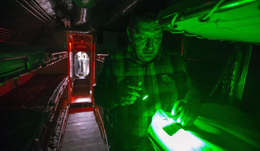 In this Saturday, Aug. 18, 2018 photo, Ramon Meza, founder and lead paranormal investigator of G.H.O.S.T. Houston, places a voice recorder on a bunk in the main berthing area aboard the USS Cavalla during an all-night investigation inside the submarine at Seawolf Park in Galveston, Texas. Some visitors claim the vessel is the scene of unexplainable phenomenon. (Stuart Villanueva/The Galveston County Daily News via AP)