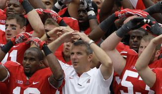 FILE - In this Sept. 1, 2012, file photo, Ohio State NCAA college football head coach Urban Meyer leads the team in singing Carmen Ohio after beating Miami of Ohio 56-10, in Columbus, Ohio.  Ohio State suspended coach Urban Meyer for three games on Wednesday night, Aug. 22, 2018, for mishandling repeated professional and behavioral problems of an assistant coach, with investigators finding Meyer protected his protege for years through domestic violence allegations, a drug problem and poor job performance. The superstar coach's treatment of his now-fired assistant was also clouded by his abiding devotion to the legacy of former Ohio State coach Earle Bruce, the grandfather of former wide receivers coach Zach Smith and an early coaching mentor for Meyer. (AP Photo/Jay LaPrete, File)