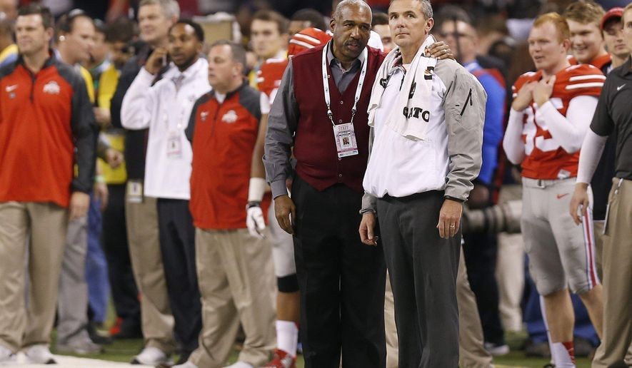 In this Dec. 6, 2014, photo, Ohio State football coach Urban Meyer, right, listens to athletic director Gene Smith near the end of the Big Ten championship football game in Indianapolis. Ohio State suspended Meyer for three games on Wednesday night, Aug. 22, for mishandling repeated professional and behavioral problems of an assistant coach. Smith was suspended without pay from Aug. 31 through Sept. 16. (Jonathan Quilter/The Columbus Dispatch via AP)