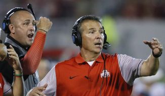 FILE - In this Sept. 17, 2016, file photo, Ohio State head coach Urban Meyer, right, and then-assistant coach Zach Smith, left, gesture from the sidelines during an NCAA college football game against Oklahoma in Norman, Okla. What has transpired over the last three weeks at Ohio State should be a lesson to all coaches. Your football program is not a family. Urban Meyer treated Zach Smith like family, and it almost cost one of the most accomplished coaches in college football his job. (AP Photo/Sue Ogrocki, File) **FILE**