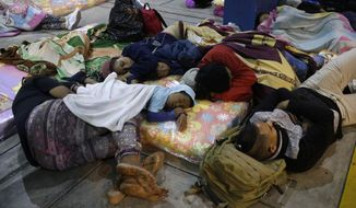 A group of Venezuelan migrants sleep on a sidewalk at a border crossing into Peru, before the deadline on new regulations that demand passports from migrants, in Tumbes, Peru, Friday, Aug. 24, 2018. Peru is stiffening its entry requirements for Venezuelan migrants beginning, Aug. 25, following the path of other South American nations receiving large numbers of Venezuelans fleeing their country's economic and human crisis, migrants will be required to enter with a passport. (AP Photo/Martin Mejia)
