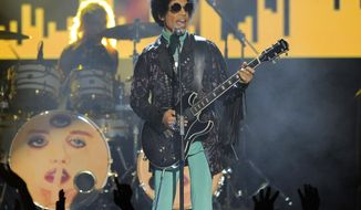 FILE - In this May 19, 2013, file photo, Prince performs at the Billboard Music Awards at the MGM Grand Garden Arena in Las Vegas. The family of the late rock star is suing a doctor who prescribed pain pills for him, saying he failed to treat him for opiate addiction and therefore bears responsibility for his death. Prince died of an accidental overdose of fentanyl in 2016. Authorities say Dr. Michael Schulenberg admitted prescribing oxycodone to Prince under his bodyguard's name to protect Prince's privacy. (Photo by Chris Pizzello/Invision/AP, File)