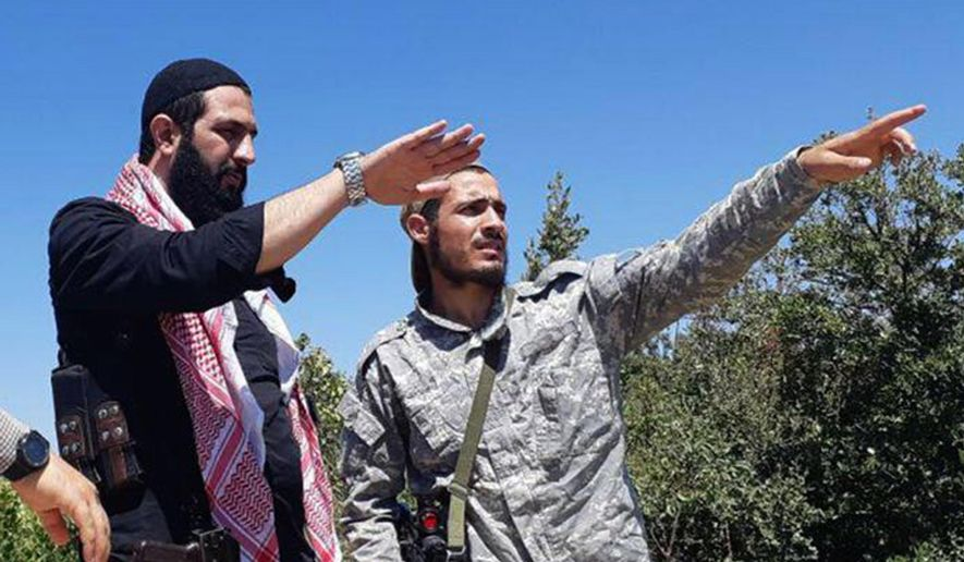 This undated photo released by the militant group Levant Liberation Committee on Tuesday, Aug. 21, 2018, shows Abu Mohammed al-Golani of the militant Levant Liberation Committee and the leader of Syria's al-Qaida affiliate, left, talking with a fighter, in the countryside of Latakia, Syria. Al-Golani vowed to fight on in Idlib province, the country's last major rebel stronghold, in the face of a possible government offensive in a video posted online to mark the Muslim feast of Eid al-Adha, shortly before midnight Tuesday, Aug. 22, 2018. (Militant UGC via AP)