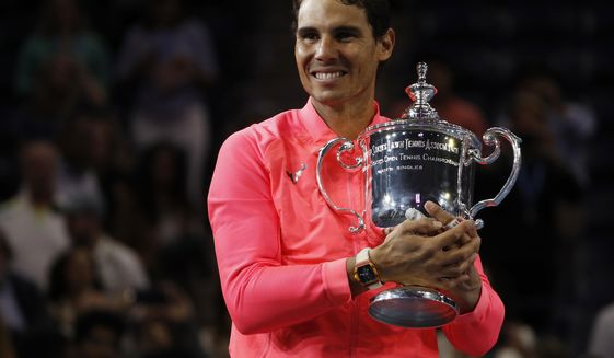 FILE - In this Sept. 10, 2017, file photo, Rafael Nadal, of Spain, holds up the championship trophy after defeating Kevin Anderson, of South Africa, in the men's singles final of the U.S. Open tennis tournament in New York. Nadal is the men's No. 1 seed at this year's U.S. Open, which starts Monday.  (AP Photo/Andres Kudack, File)