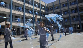 """FILE - In this March 12, 2018, file photo, refugee school girls fly kites during the """"Kites of Dignity"""" event at the UNRWA Rimal Girls Preparatory school in Gaza City. The Trump administration has decided to cut more than $200 million in bilateral to the Palestinians, following a review of the funding for projects in the West Bank and Gaza, according to U.S. officials and congressional aides. (AP Photo/Adel Hana, File)"""