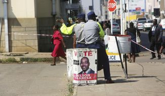 A police officer directs pedestrians  while seated on a bin with a campaign poster of opposition leader Nelson Chamisa on a street, in Harare, Friday, Aug. 24, 2018.  Zimbabwe's constitutional court was set to rule Friday afternoon on the main opposition's challenge to the results of last month's historic presidential election. Security was tight in the capital, Harare, as the court will determine whether President Emmerson Mnangagwa's narrow victory is valid. The opposition claims vote-rigging and seeks either a fresh election or a declaration that its candidate, 40-year-old Nelson Chamisa, won. (AP Photo/Tsvangirayi Mukwazhi)