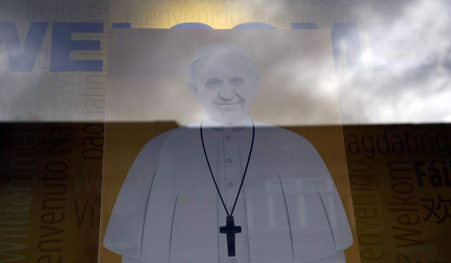 An image of Pope Francis is displayed in the window of the Veritas religious bookshop in Dublin, Ireland, Friday, Aug. 24, 2018. Pope Francis arrives on Saturday for a two-day visit to Ireland. (AP Photo/Matt Dunham)