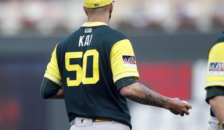 "Oakland Athletics' starting pitcher Mike Fiers wears his nickname ""Kai"" on his jersey as he finished a visit with catcher Jonathan Lucroy in the first inning of a baseball game against the Minnesota Twins, Saturday, Aug. 25, 2018, in Minneapolis. (AP Photo/Jim Mone)"