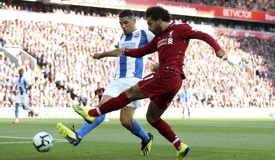 Brighton & Hove Albion's Steve Sidwell, background and Liverpool's Mohamed Salah battle for the ball, during the English Premier League soccer match between Liverpool and Brighton,  at Anfield, in Liverpool, England, Saturday, Aug. 25, 2018. (Martin Rickett/PA via AP)