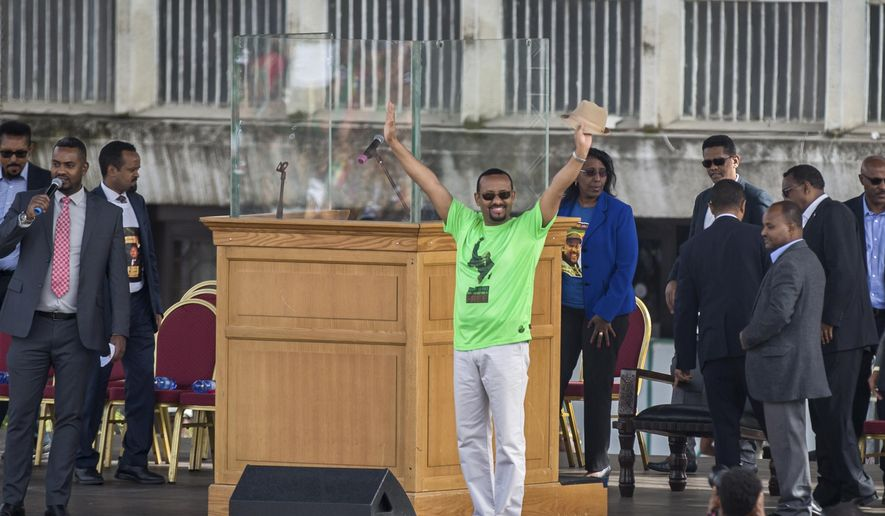 """FILE - In this Saturday, June 23, 2018 file photo, Ethiopia's Prime Minister Abiy Ahmed waves to the crowd at a large rally in his support, in Meskel Square in the capital, Addis Ababa, Ethiopia. Ahmed in his first press conference since taking power vowed Saturday, Aug. 25, 2018 to continue with reforms """"at any cost"""" and says the longtime ruling coalition soon will prepare for a """"free and fair election"""" in 2020. (AP Photo/Mulugeta Ayene, File)"""