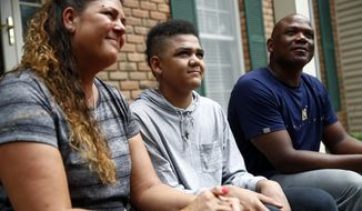 In this Aug. 18, 2018, photo, Jarren Jasper, center, sits on his family's front porch with his mother Donna, left, and father Ivin, offensive coordinator of the Navy football team, in Arnold, Md. The Jaspers endured a six-month ordeal that ultimately ended with Jarren getting a heart transplant late last January. All is well now with the Jaspers, although the memories of what they endured won't ever fade. (AP Photo/Patrick Semansky)