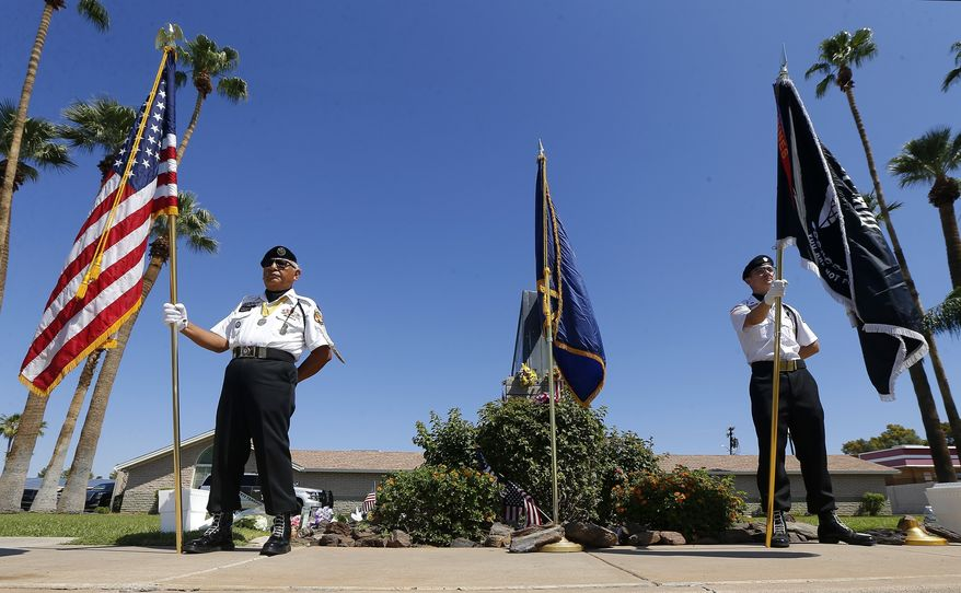 Members of the POW-MIA-KIA Honor Guard organization stand in front of a local mortuary keeping the late Arizona Sen. John McCain, Sunday, Aug. 26, 2018, in Phoenix. McCain, the war hero who became the GOP's standard-bearer in the 2008 election, died Saturday, Aug. 25, 2018, after battling brain cancer. He was 81. (AP Photo/Ross D. Franklin)