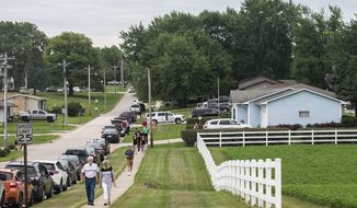 People walk several blocks to attend Mollie Tibbetts' funeral at Brooklyn-Guernsey-Malcom High School after the parking lot outside the school had been filled, Sunday, Aug. 26, 2018, in Brooklyn, Iowa. Cristhian Bahena Rivera is charged with first-degree murder in Tibbetts' death. Authorities have said Tibbetts was abducted while running in July, and an autopsy showed that she died from stab wounds. (Kelsey Kremer/The Des Moines Register via AP)