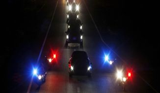 With a police escort, a procession follows the hearse carrying the late Arizona Sen. John McCain along Interstate 17 on the way to Phoenix, Saturday, Aug. 25, 2018, in Anthem, Ariz. (AP Photo/Ross D. Franklin)