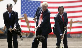 FILE - In this June 28, 2018, file photo, President Donald Trump, center, along with Wisconsin Gov. Scott Walker, left, and Foxconn Chairman Terry Gou participate in a groundbreaking event for the new Foxconn facility in Mt. Pleasant, Wis. To make the next generation of liquid crystal display technology, Foxconn Technology Group will draw talent from beyond the borders of Wisconsin, partner with universities and technical schools and even tap into transitioning members of the military to find the 13,000 workers it eventually expects to hire. (AP Photo/Evan Vucci, File)
