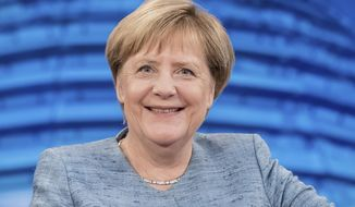 German Chancellor Angela Merkel poses for media after she arrives for the annual 'Summer Interview' with the German public broadcasting service ARD in Berlin, Germany, Sunday, Aug. 26. 2018. (Michael Kappeler/dpa via AP)