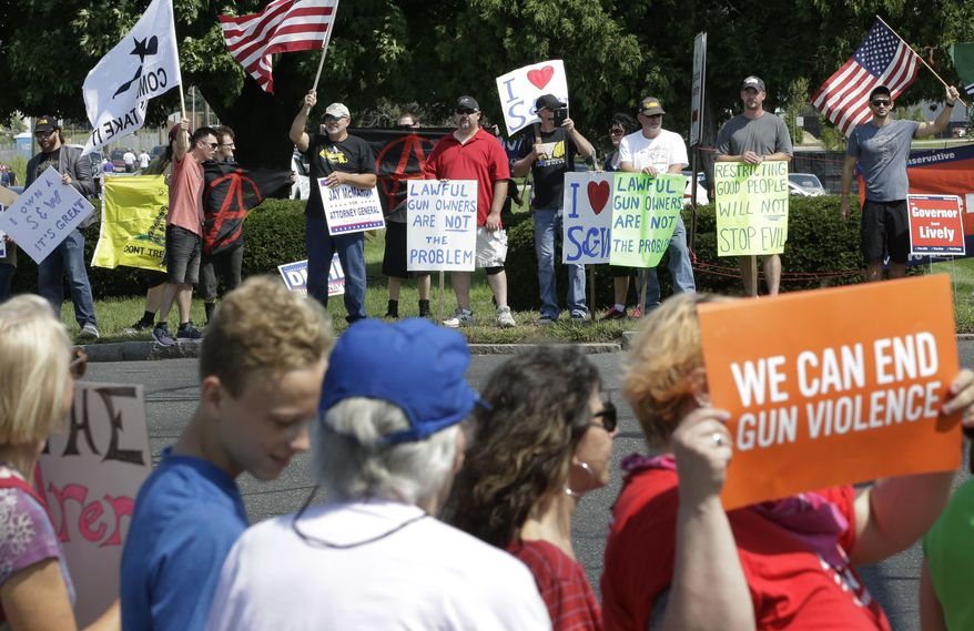 Demonstrators supporting gun law reforms, foreground, walk on the opposite side of the road from counter protesters supporting Second Amendment rights, behind, near the headquarters of gun manufacturer Smith & Wesson, Sunday, Aug. 26, 2018, in Springfield, Mass. The 50-mile march supporting gun law reforms, began Thursday, Aug. 23, 2018, in Worcester, Mass., and ended Sunday, in Springfield, with a rally near the headquarters of the gun manufacturer. (AP Photo/Steven Senne)