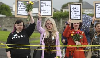 People hold up names of children as they gather to protest at the site of the former Tuam home for unmarried mothers in County Galway, during the visit to Ireland by Pope Francis, Sunday, Aug. 26, 2018. Survivors of one of Ireland's wretched mother and baby homes were to hold their own demonstration Sunday. The location is Tuam, site of a mass grave of hundreds of babies who died at a church-run home. (Niall Carson/PA via AP)