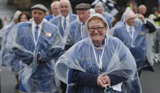 People wait for the arrival of Pope Francis in front of the Knock Shrine, in Knock, Ireland, Sunday, Aug. 26, 2018. Pope Francis is on a two-day visit to Ireland. (Niall Carson/PA via AP)