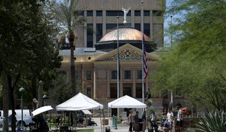 As flags fly at half-staff at the Arizona Capitol in memory of the late Arizona Republican Sen. John McCain, television crews broadcast live Sunday, Aug. 26, 2018, in Phoenix. McCain, the war hero who became the GOP's standard-bearer in the 2008 election, has died at the age of 81, Saturday, Aug. 25, 2018, after battling brain cancer. (AP Photo/Ross D. Franklin)