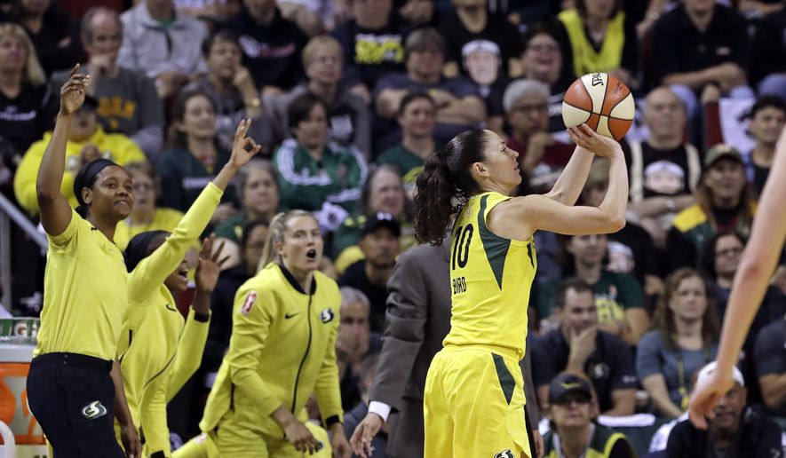 Seattle Storm's Sue Bird, right, shoots a three-point basket as teammates cheer on the bench in the first half of a WNBA basketball playoff semifinal against the Phoenix Mercury, Sunday, Aug. 26, 2018, in Seattle. (AP Photo/Elaine Thompson)