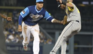 Los Angeles Dodgers shortstop Manny Machado tags out San Diego Padres' Travis Jankowski during the 10th inning of a baseball game Saturday, Aug. 25, 2018, in Los Angeles. (AP Photo/Michael Owen Baker)