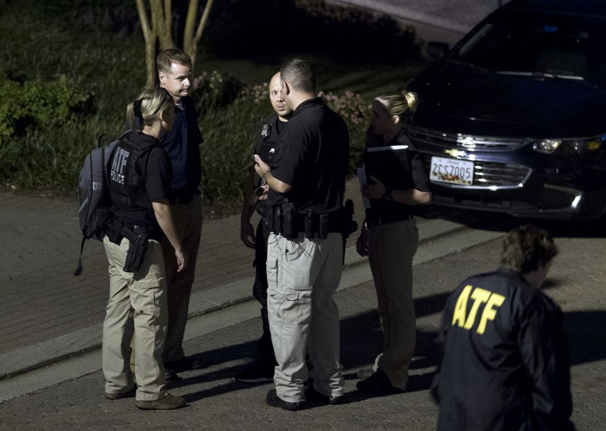 Agents with the Bureau of Alcohol, Tobacco, Firearms and Explosives leave the family home, in Baltimore, Sunday, Aug. 26, 2018, of the suspect in a mass shooting earlier in the day in Jacksonville, Fla. (AP Photo/Jose Luis Magana)