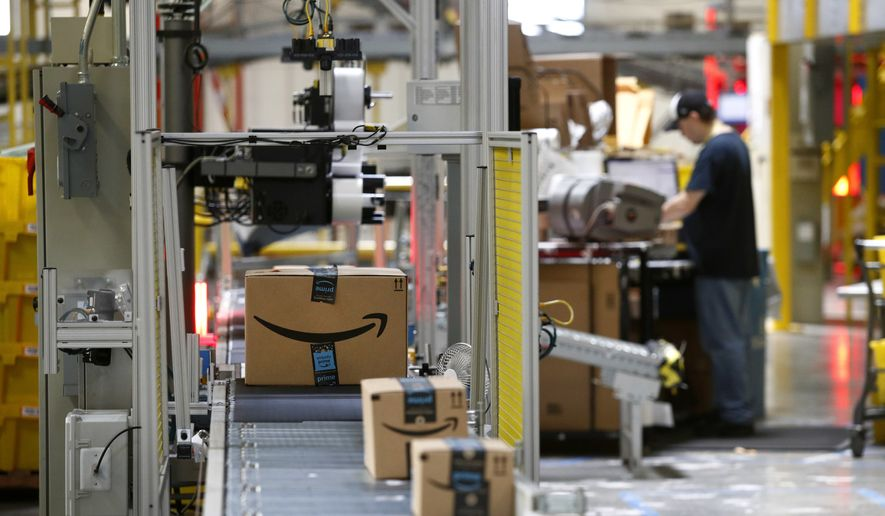 FILE- In this Aug. 3, 2017, file photo, packages pass through a scanner at an Amazon fulfillment center in Baltimore. Amazon is paying workers to defend the company on Twitter, reassuring critics that they make enough money to live and are allowed to take bathroom breaks. The tweets are part of Amazons plan to combat negative headlines and online chatter about poor working conditions at its warehouses. (Photo/Patrick Semansky, File)