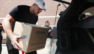 In this Sunday, Sept. 3, 2017, photo, Houston Texans defensive end J.J. Watt places a box of relief supplies in the back of a vehicle to people impacted by Hurricane Harvey, in Houston. Watt said Monday, Aug. 27, 2018, that he has distributed the $41.6 million his foundation raised to help rebuild the Texas Gulf Coast after Hurricane Harvey. (Brett Coomer/Houston Chronicle via AP, Pool)
