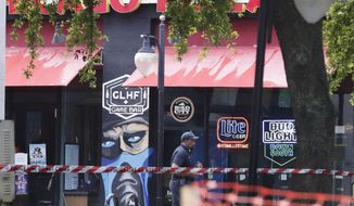 A police officer walks by the front of a Chicago Pizza and GLHF Game Bar on Monday, Aug. 27, 2018, at the scene of fatal shooting on Sunday, at The Jacksonville Landing in Jacksonville, Fla. A gunman opened fire at a video game tournament killing multiple people and then fatally shooting himself in a rampage that wounded several others. (AP Photo/John Raoux)