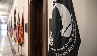 A POW/MIA flag stands outside the office of Arizona Sen. John McCain in the Russell building on Capitol Hill in Washington, Monday, Aug. 27, 2018. McCain, a prisoner of war in Vietnam, a two-time Republican presidential contender and towering figure in Congress, died Saturday at age 81 of brain cancer. (AP Photo/J. Scott Applewhite)
