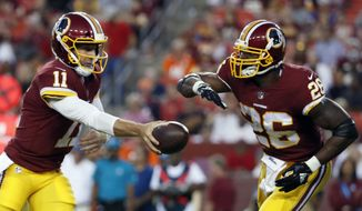 FILE - In this Aug. 24, 2018, file photo, Washington Redskins quarterback Alex Smith (11) hands the ball off to running back Adrian Peterson during the first half of a preseason NFL football game against the Denver Broncos in Landover, Md. The Redskins acquired Smith, a winner wherever he's played, after last season. Peterson has a shot to be a featured back once again. (AP Photo/Alex Brandon, File) **FILE**