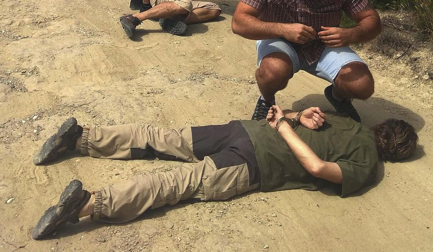In this image released by the Spanish National Police on Monday Aug. 27, 2018, alleged suspect Jos Brech is detained by Spanish police officers in the countryside of the province of Barcelona, north-eastern Spain. Dutch police say a suspect in the slaying 20 years ago of an 11-year-old boy has been detained in Spain following an appeal to the public for help tracking him down. Police say in a written statement that the suspect, 55-year-old Jos Brech, was detained Sunday afternoon and is being held pending his transfer to the Netherlands. (Spanish National Police via AP)